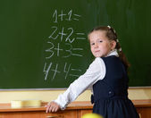 Little proud schoolgirl at blackboard — Stock Photo