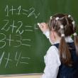 Little schoolgirl writing on blackboard — Stock Photo