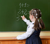 Little happy schoolgirl writing on blackboard — Stock Photo