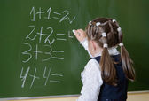 Little schoolgirl writing on blackboard — Stock Photo