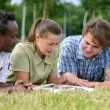 International students reading in park — Stock Photo