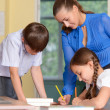 Teacher helping schoolchildren — Stock Photo