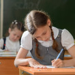 Little pretty schoolgirl writing in class — Stock Photo