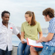 Three students discussing a difficult problem on stone promenade — Stock Photo