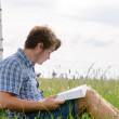 Student boy reading a big book sitting on grass — Stockfoto