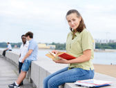 Student girl reading on stone promenade — Stock Photo