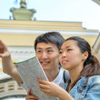Young tourists studying map — Stock Photo