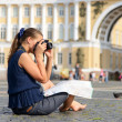 Female tourist sitting on pavement — Stock Photo