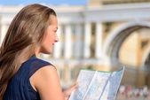 Female tourist sitting on pavement — Stock Photo