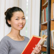 Smiling female student standing by bookshelf in library — Stok fotoğraf