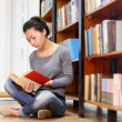 Student girl reading studying in library — Stock Photo