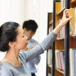 Student girl choosing books on bookshelf — Stock Photo
