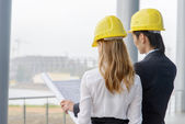 Two young designers on construction site — Stock Photo