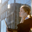 Businesswoman using laptop and talking on the phone outdoors — Stock Photo
