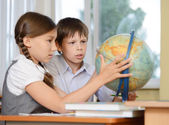 Two shcoolchildren looking at globe — Stock Photo