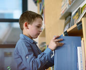 Little schoolboy taking a book from a bookshelf in a library — Stock Photo