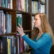 Beautiful student girl in a library — Stock Photo