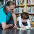 Father and son sitting by bookshelf in a library and reading a b — Stock Photo