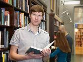 Élève de sexe masculin dans une bibliothèque — Photo