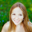 Beautiful red-haired smiling young woman sitting on the grass — Stock Photo #23939943