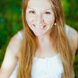 Adorable red-haired smiling young woman sitting on the grass — Stock Photo