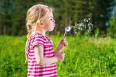 очаровательны блондинка маленькая девочка, дует одуванчика — Стоковое фото