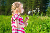 Adorable blond little girl blowing a dandelion — Stok fotoğraf