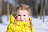 Adorable little girl in a yellow winter jacket — Stock Photo