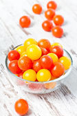 Red and yellow fresh cherry tomatoes with water drops in glass b — Stock Photo