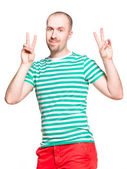 Young cheerful man with v sign in striped white and turquoise t-shirt and orange jeans isolated on white — Stock Photo