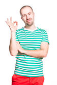 Young cheerful smiling man with ok gesture in striped white and turquoise t-shirt and orange jeans isolated on white — Stock Photo