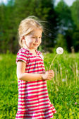 Cute smiling little girl with dandelion in her hands makes wish — Stock Photo