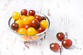 Brown and yellow fresh cherry tomatoes with water drops in glass bowl on wooden table — Stock Photo