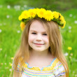 Portrait of a beautiful blond little girl with a floral head wreath — Stock Photo