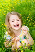 Laughing blond little girl with closed eyes sitting in the grass — Stock Photo