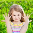 Cute smiling blond little girl with many-coloured manicure — Stock Photo #26235437