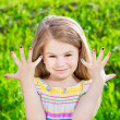 Cute smiling blond little girl with many-coloured manicure — Stock Photo