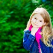 Outdoor portrait of a beautiful blond little girl wearing a jeans jacket and a pink scarf — Stock Photo