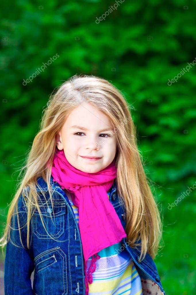 室外肖像的可爱微笑着的金发小女孩穿着牛仔裤外套色