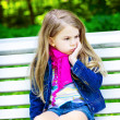 Sad blond little girl sitting on a bench in the park — Stock Photo