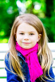 Closeup portrait of a beautiful smiling blond little girl in the — Stock Photo