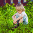 Portrait of a handsome sad little boy sitting on grass near his school — Stock Photo
