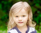 Closeup portrait of an adorable little girl with blond curly hair in summer day — Stock Photo