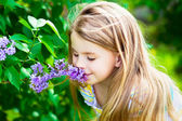 Beautiful blond little girl with long hair smelling flower — Stock Photo