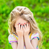 Beautiful smiling blond little girl with long hair and many-coloured manicure covering her eyes with her hands — Stock Photo