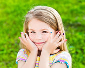 Adorable smiling blond little girl with long hair and many-coloured manicure — Stock Photo