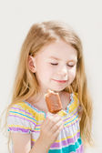 Adorable blond little girl with long hair eating ice-cream in summer sunny day — Stock Photo