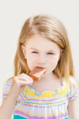 Beautiful blond little girl with long hair eating ice-cream in summer sunny day — Stock Photo