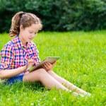 Outdoor ritratto di una ragazza adolescente carina in abiti casual, seduto sull'erba con tavoletta digitale sulle sue ginocchia, lettura e surf — Foto Stock #29132323