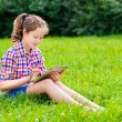 Outdoor portrait of pretty teenager girl in casual clothes sitting on grass with digital tablet on her knees, reading and surfing — Stock Photo #29132323